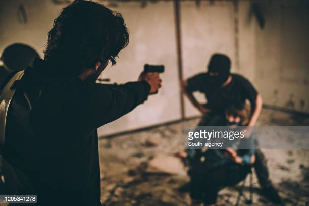 detective saving a hostage - machine gun stock pictures, royalty-free photos & images