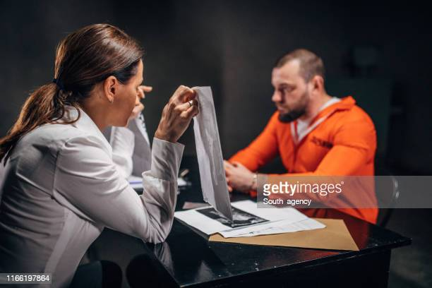detective showing photographs to a man prisoner in interrogation room - confession law stock pictures, royalty-free photos & images