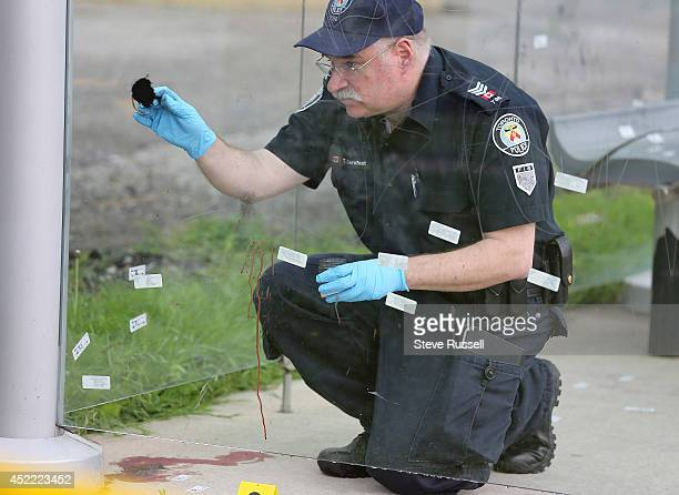 Detective Todd Carefoot with the Forensic Identification dusts for finger prints as Police investigate a murder in a bus shelter at the corner of...