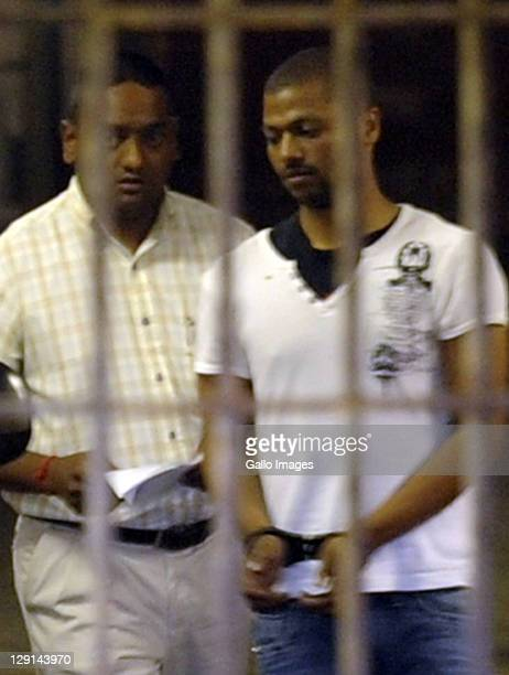 Detective Warrant Officer Shane Naidoo leads Thabo Bester aka the Facebook Rapist out of the holding cells at the Durban Magistrates Court on October...