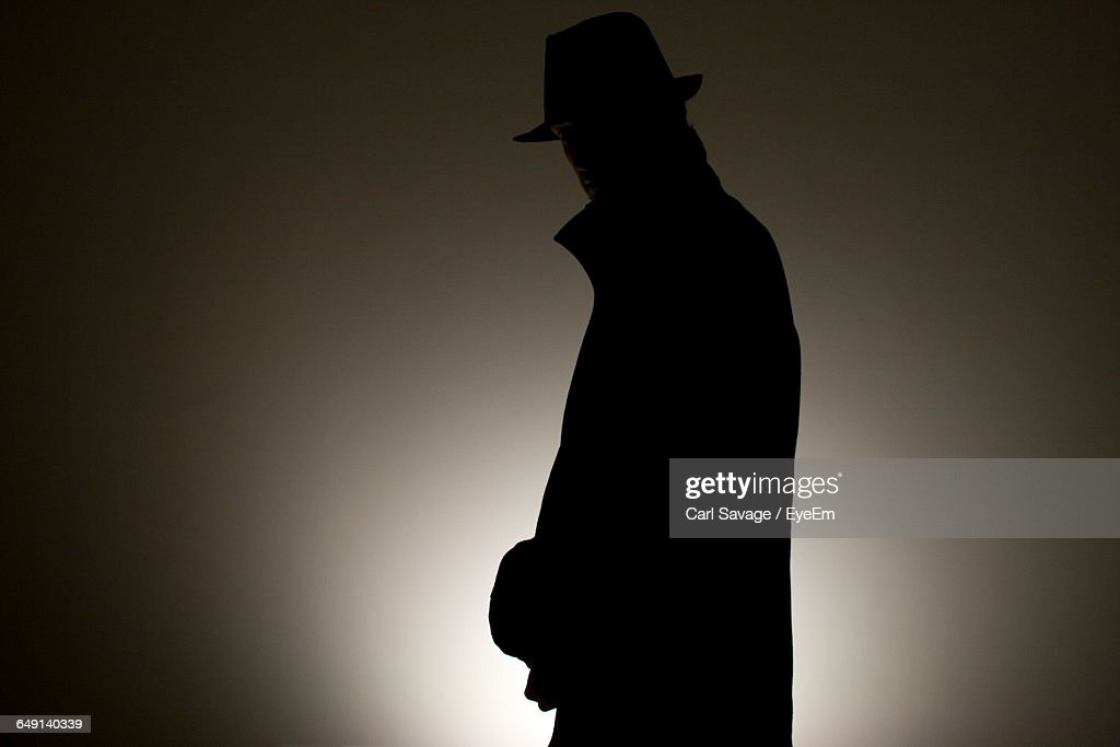 Detective Wearing Hat Against Wall In Room : Stock Photo