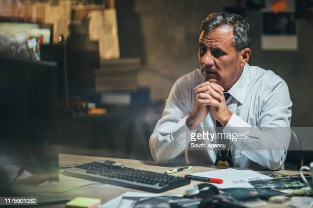 detective working at night in office - police chief stock pictures, royalty-free photos & images