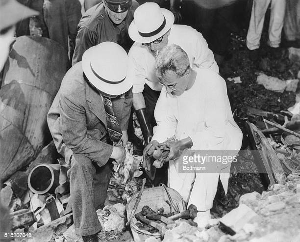 Detectives and Coroner S Gerber examine bones of two murder victims found at the East 9th Street Lakeshore Dump on August 16 1938 in Cleveland Ohio...