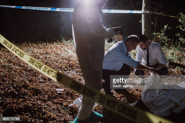 Detectives and forensics examining murder scene at night