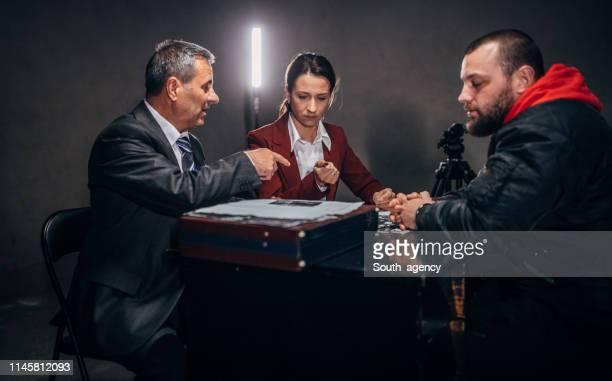 取り調べ室に座っている探偵と雄の囚人 - 執行猶予 ストックフォトと画像