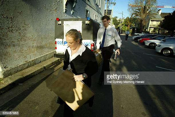 Detectives carry envelopes of evidence into Redfern police station after a search warrant was executed on the Redfern apartment of a private school...