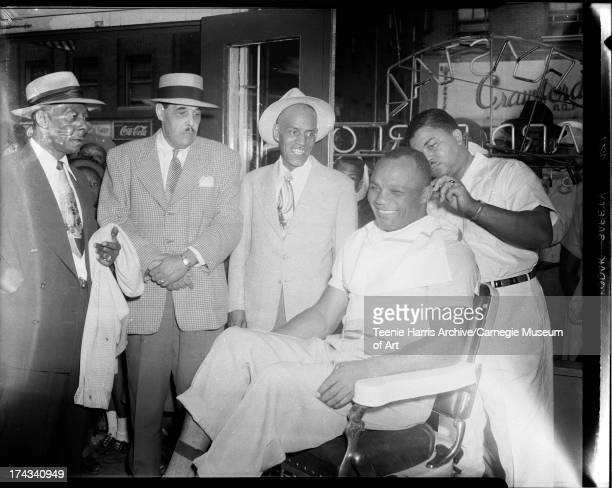 Detectives Eugene Parker James Voyle Parker and John B Thompson watching barber Clarence 'Speedy' Williams cut hair of boxer Jersey Joe Walcott in...