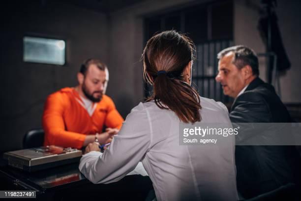 尋問室で男性囚人を尋問する刑事 - 執行猶予 ストックフォトと画像