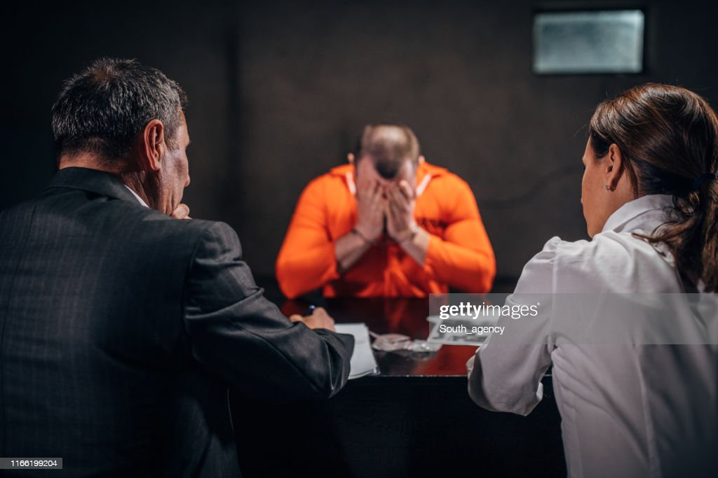 Detectives interrogating a man prisoner : Stock Photo