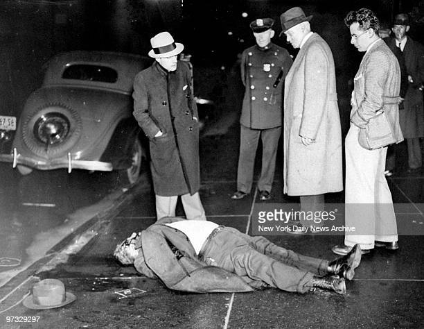 Detectives look over the body of gangster Michael Sisto after he was shot gangland style at President St and Fourth Ave
