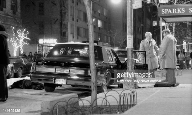 Detectives stand over body of reputed mob boss Paul Castellano after execution on 46th St Body of Castellano's chauffeur Thomas Bilotti lies...
