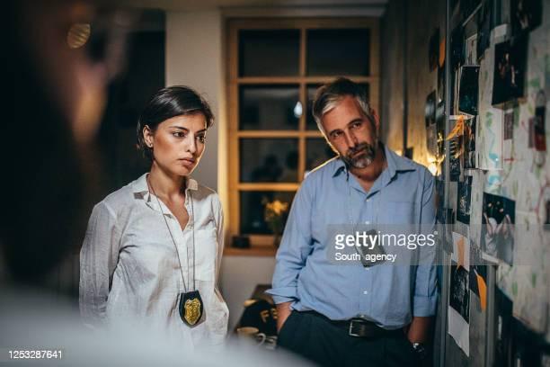 オフィスで事件に取り組んでいる探偵 - 警察署長 ストックフォトと画像