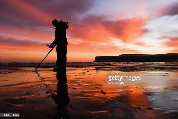 A detectorist sweeps the sand on the beach with his metal detector as clouds light up dramatically at sunrise on January 2 2018 in SaltburnByTheSea...