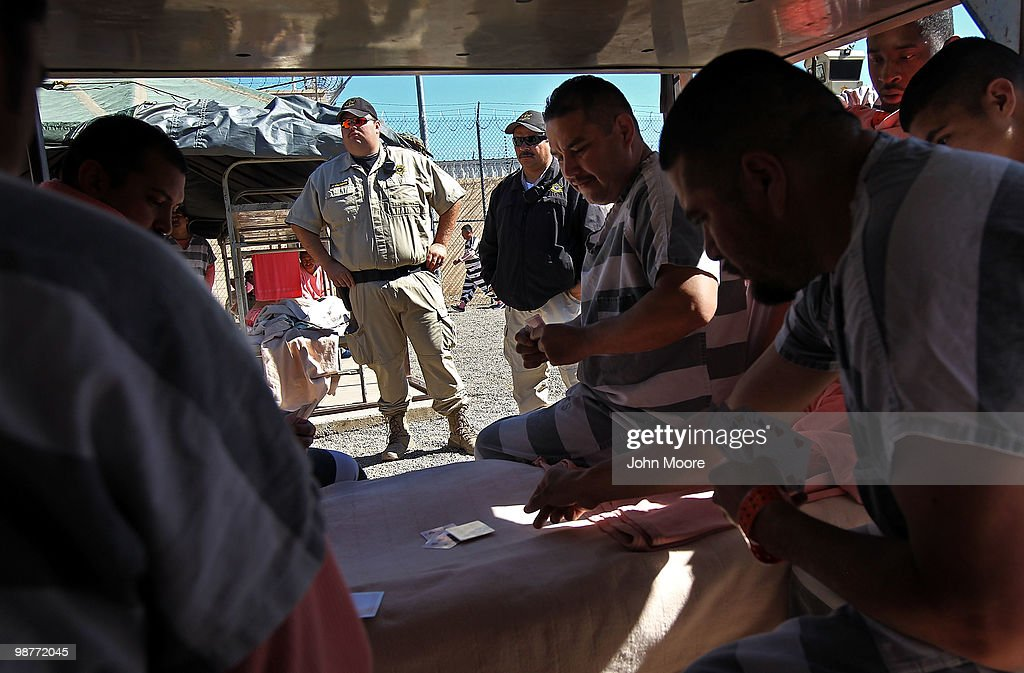 Detention officers watch as undocumented immigrants play cards in their tent at the Maricopa County Tent City Jail on April 30, 2010 in Phoenix, Arizona. Some 200 undocumented immigrants are currently serving time in the facility, and most will be deported to Mexico after serving their sentence. The controversial jail is run by Maricopa County Sheriff Joe Arpaio, who has been an outspoken critic of illegal immigration and a supporter of Arizona's new tough immigration law. Prisoners at the facility are fed twice a day, sleep in non-airconditioned tents and are issued striped prison uniforms and pink underwear and socks.