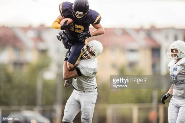 determined american football player catching offense player during the game. - wide receiver athlete stock pictures, royalty-free photos & images