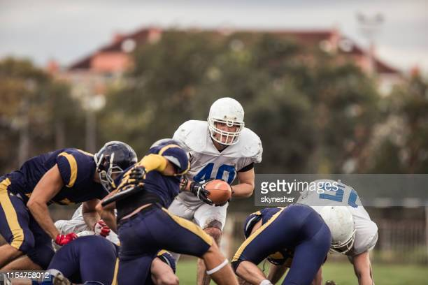 determined american football player during a match on playing field. - american football team stock pictures, royalty-free photos & images