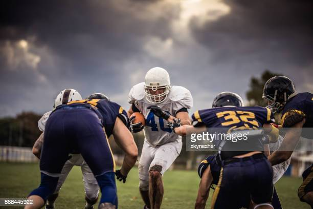 determined american football player making an effort while passing through defense players. - attaccante foto e immagini stock