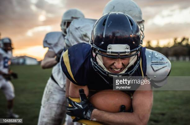determined american football player passing defensive players on a match. - american football strip stock pictures, royalty-free photos & images