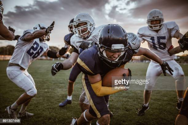 determined american football player passing defensive players on a match. - wide receiver athlete stock photos and pictures