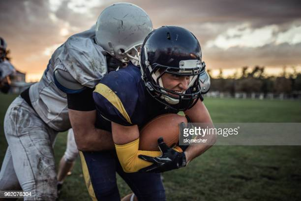 determined american football player trying to pass defensive player on a match. - tackle american football player stock pictures, royalty-free photos & images
