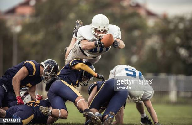 determined american football player with a ball trying to score touchdown. - american football strip stock pictures, royalty-free photos & images