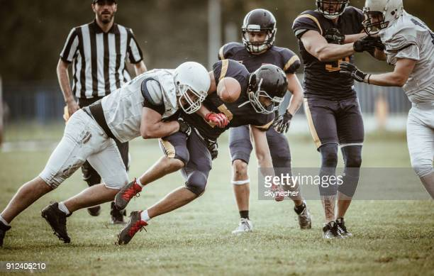 determined american football players tackling during the game on playing field. - american football referee stock pictures, royalty-free photos & images