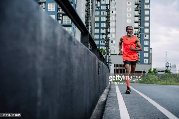 determined and motivated: a senior african american man in red sportswear running in the city - over 80 stock pictures, royalty-free photos & images