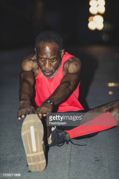 determined and motivated: a senior man in red sportswear warming up for a night training in the city - over 80 stock pictures, royalty-free photos & images