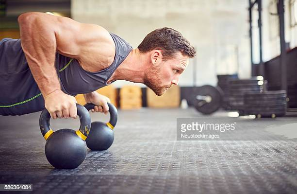 determined athlete doing push-ups on kettlebells in gym - dureza - fotografias e filmes do acervo