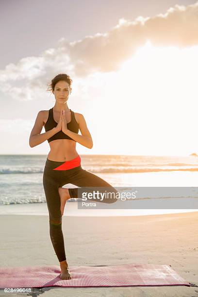 Determined athlete doing yoga in tree pose