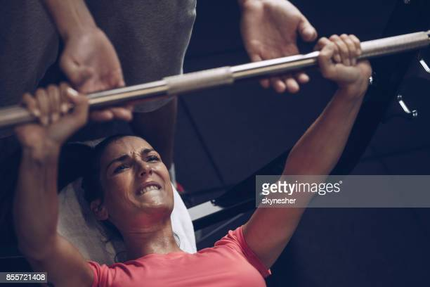 Determined athlete making an effort while doing bench press exercises with her coach.