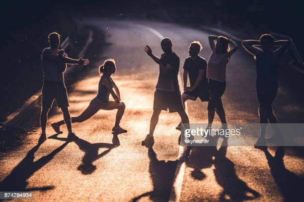 Determined athletes doing stretching exercises before marathon race at sunset.