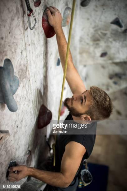 Sportlichen Mann klettert die Wand in Bouldern Turnhalle bestimmt.