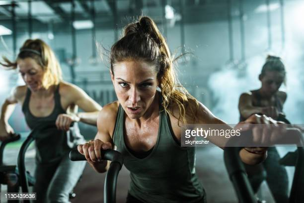 determined athletic woman during exercise class on bike in a gym. - peloton stock pictures, royalty-free photos & images