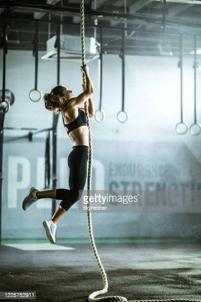 determined athletic woman moving up the rope in a gym. - cross training stock pictures, royalty-free photos & images