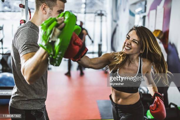 determined athletic woman on a boxing training with her coach in a gym. - martial arts stock pictures, royalty-free photos & images