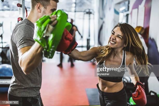 ジムで彼女のコーチとボクシングのトレーニングで運動女性を決定しました。 - 武道 ストックフォトと画像