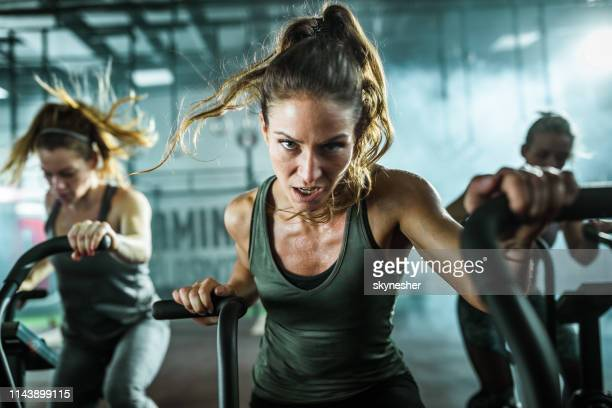 determined athletic woman on stationary bike during cross fit training in a gym. - effort stock pictures, royalty-free photos & images