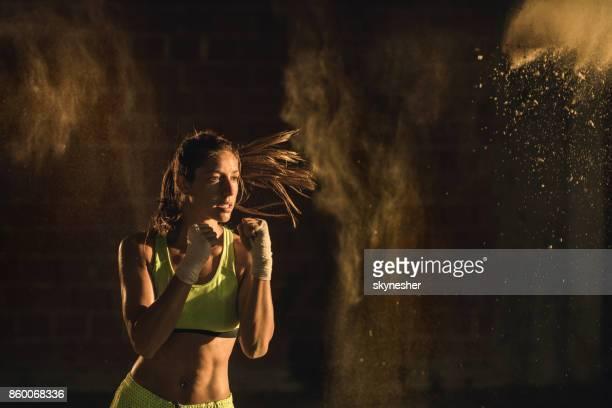 determinada mulher atlética de aquecimento com exercícios de boxe. - boxe feminino - fotografias e filmes do acervo