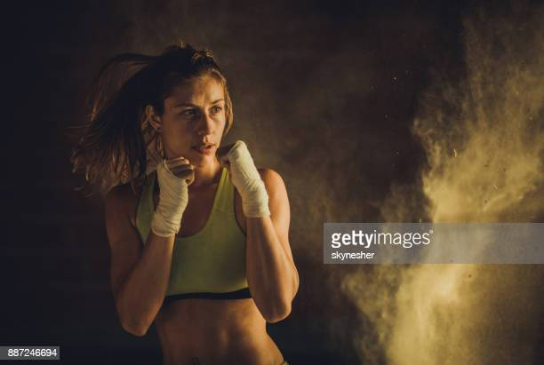 Determined athletic woman warming up with boxing exercises.