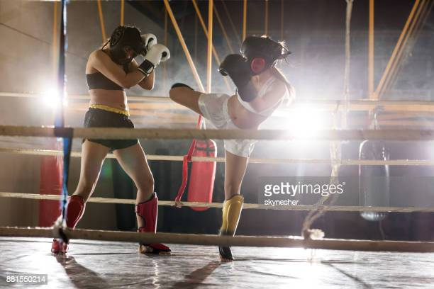 Determined athletic women fighting on a kickboxing match.