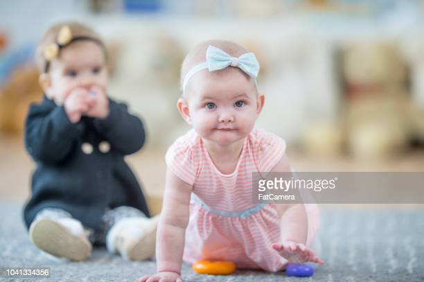 determined baby girl crawls towards the camrea - hair bow stock pictures, royalty-free photos & images