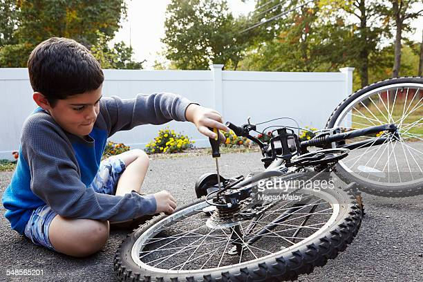 Determined boy repairing bicycle on driveway