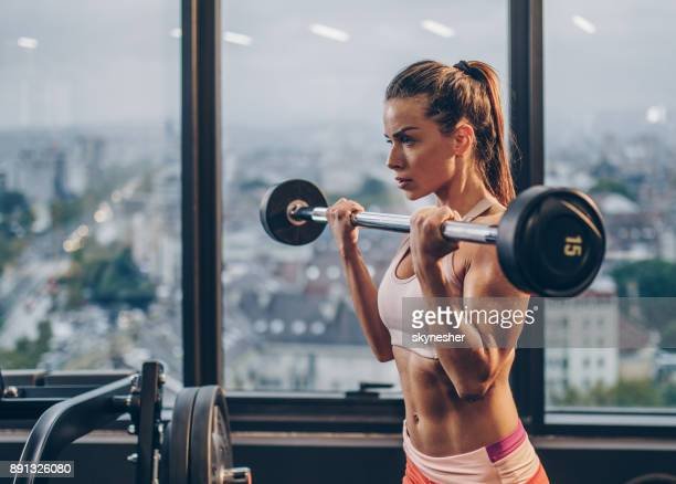 Determined female athlete having a weight training in a health club.