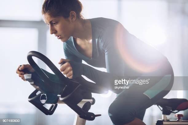Athlète féminine déterminée sur un cours de spinning dans un club de santé.
