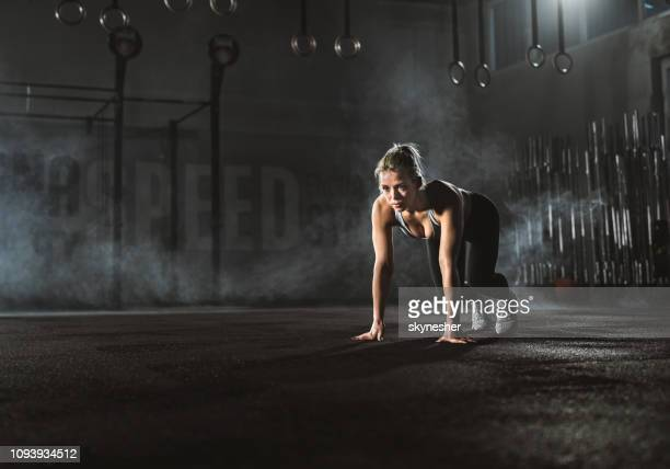 determined female athlete on starting line in a health club. - active lifestyle stock pictures, royalty-free photos & images