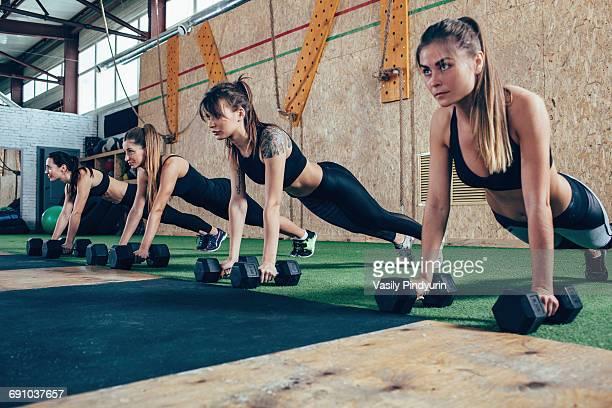 Determined female athletes doing push-ups on dumbbells at health club