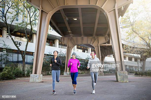 Determined female athletes jogging under bridge
