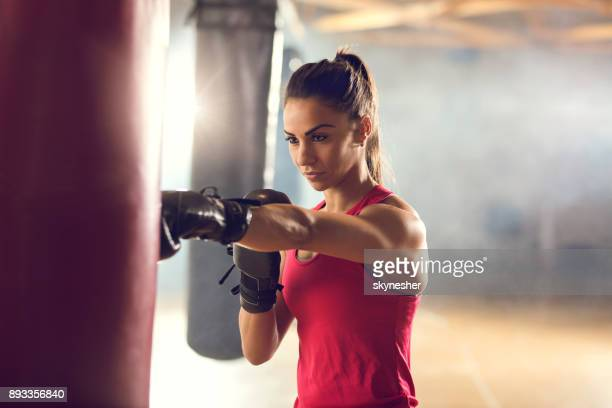 Determined female boxer exercising on a sports training in a health club.