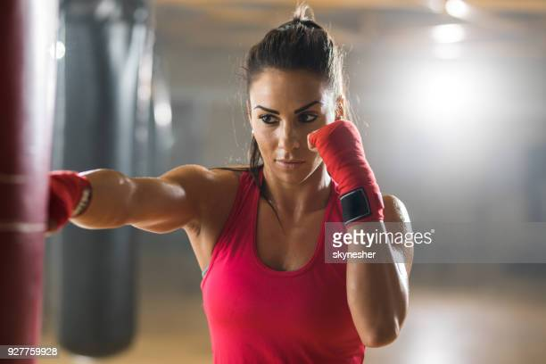 determined female boxer exercising on a sports training in a health club. - muay thai imagens e fotografias de stock